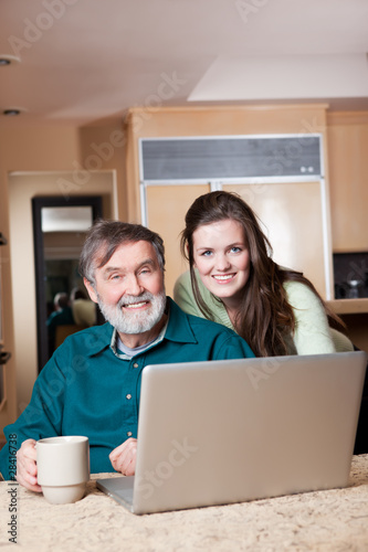 Teenage girl with grandpa using laptop