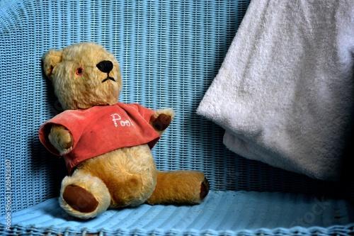 Leinwanddruck Bild Beloved Winnie the Pooh sits in a chair