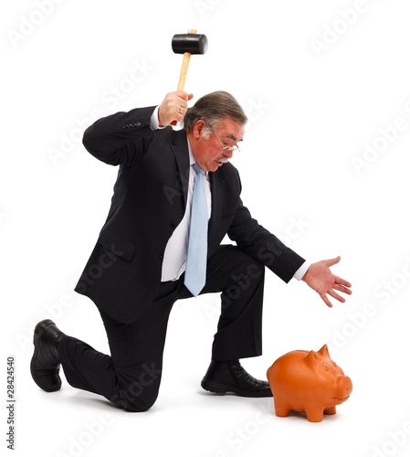 Business man breaking piggy bank