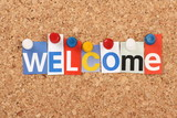 The word Welcome in magazine letters on a notice board poster