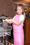 little girl taken clear glass from dishwasher in the kitchen