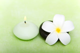 Candle, spa stone and frangipani flower