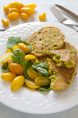 Homemade chickpea flour pancakes with fresh yellow tomatoes