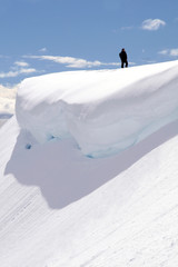 Man Standing on Edge of Snowy Cliff