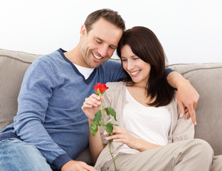 Portrait of a lovely couple looking at a red rose