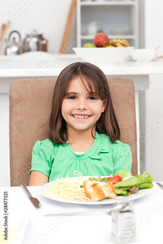 Cute little girl eating pasta and salad