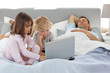 Attentive boy using a laptop with his sister while their parents