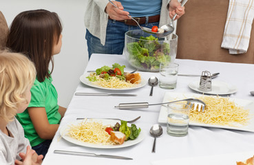 Mother serving salad to her children at lunch