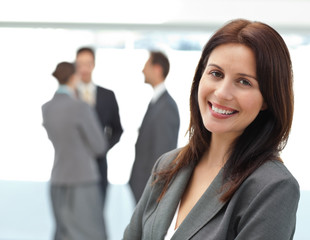 Pretty businesswoman posing in front of her team while working