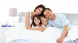 Happy children with their parents on the bed