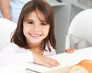 Cute little girl eating bread during breakfast