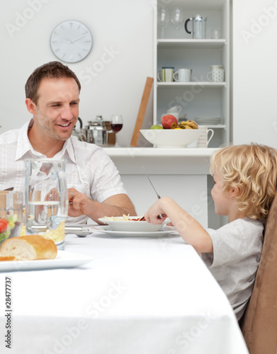 Proud dad talking to his son while eating pasta together