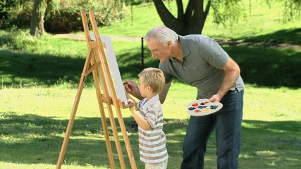 Little boy painting a white canvas with grandfather