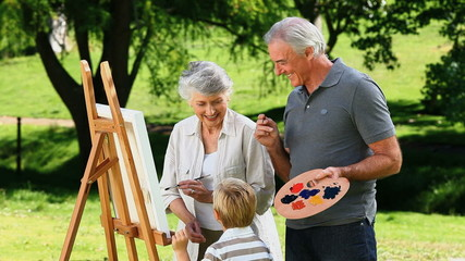 Boy and grandparents painting a white canvas