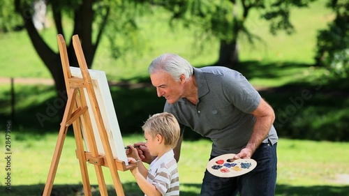 Young boy painting a white canvas with grandad