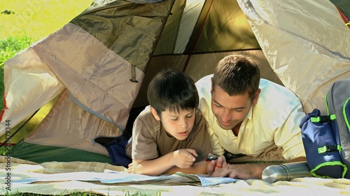 Dad and son looking at a map in front of a tent