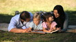 Family reading a book lying on the grass