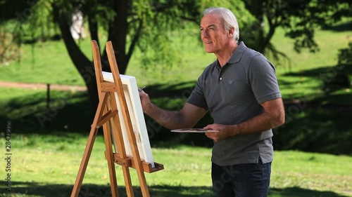 Senior male painting a canvas