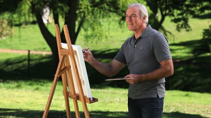 Old male painting a canvas