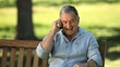 Elderly man talking on the phone on a bench
