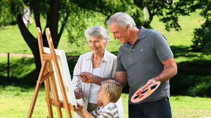 Young boy and grandparents painting a canvas