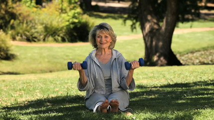 Senior woman working her muscles with dumbbells on the grass