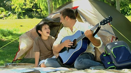Father playing guitar for his son in front of a tent