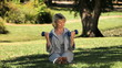 Old woman working her muscles with dumbbells sitting on the grass