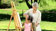 Young child painting a canvas with grandmother