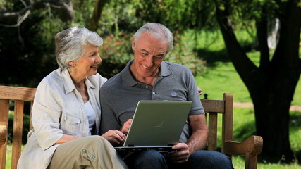 Senior couple looking at a laptop sitting on a bench
