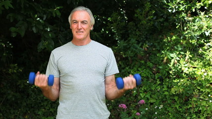 Elderly man working her muscles with dumbbells