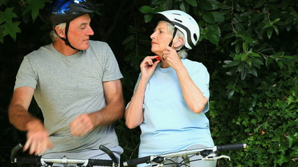 Elderly couple with bikes tying their helmets