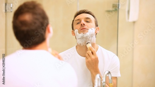 Handsome man shaving his beard in front of a mirror