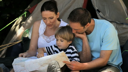 Family looking at a map near a tent