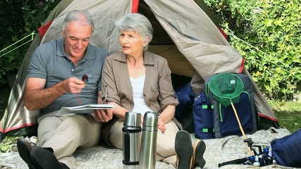 Seniors looking at a map sitting near a tent