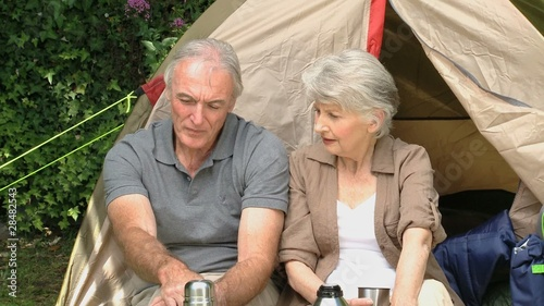 Seniors talking together in front of a tent