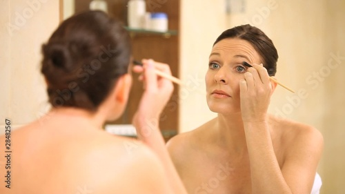 Beautiful woman applying eye makeup