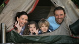 Family smilling at the camera in a tent