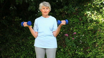 Old woman working her muscles with dumbbells