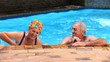Aged couple swimming in the pool