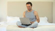 Man working on a laptop sitting on the bed