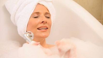 Beautiful woman singing in a bathtub