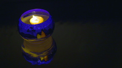Floating candles in a candlestick with Christmas pattern