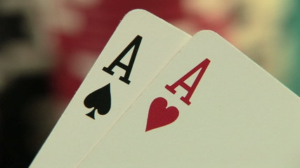 Pocket aces in a deck of playing cards with poker chips