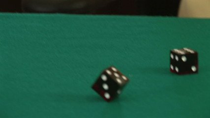 Hands rolling a pair of dice on a poker table