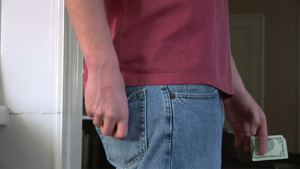 Close up of male putting wallet in back pocket of jeans