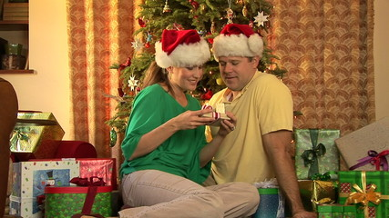 Young couple exchanging presents by Christmas tree