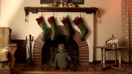 Toddler in pajamas looking for Santa in the fireplace