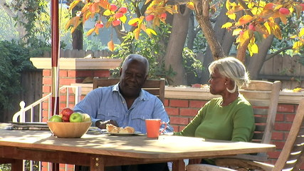 Senior couple having coffee and breakfast outdoors on the patio