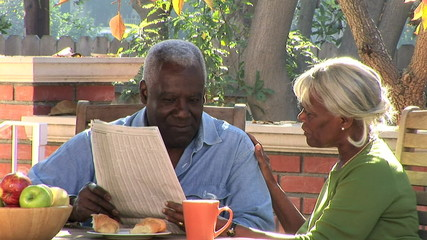 Senior couple reading the newspaper on the patio
